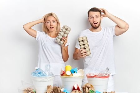 close up portrait of puzzled woman and man holding carton egg pack on white background. Recycle concept. emotion and feeling