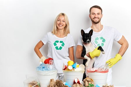 young active ambitious volunteers taking care of animals and nature, young couple holding a dog and posing to the camera while standing behind the recycling bins