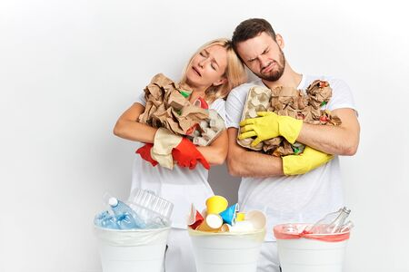Recycling and plastic pollution problem concept. unhappy crying man and woman hugging rubbishl leaning on each other . family worries about ecological problem, global problem Banco de Imagens