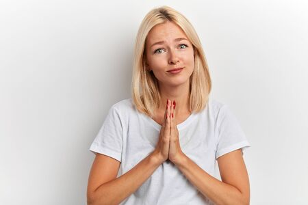 kind friendly fair-haired woman prays for wellness of her family, keeps palms pressed together, against white background. People, faith, hope, help me