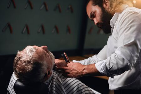 bearded stylist brusing the hair of his client, close up side view photo