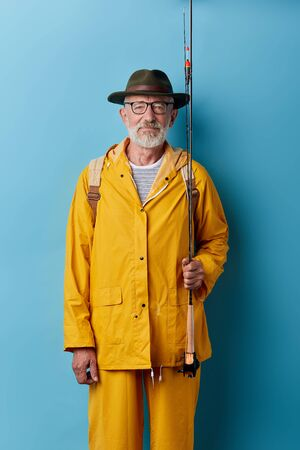 senior man in green hat and yelow raincoat holding fishing rod and posing to the camera, close up photo. pastime, leisure