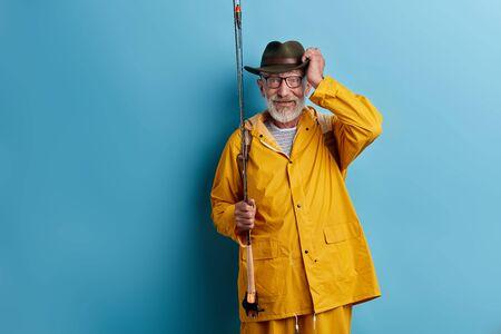 souriant vieil homme heureux profitant de son passe-temps, grand-père menant un mode de vie actif. fond bleu isolé, tourné en studio