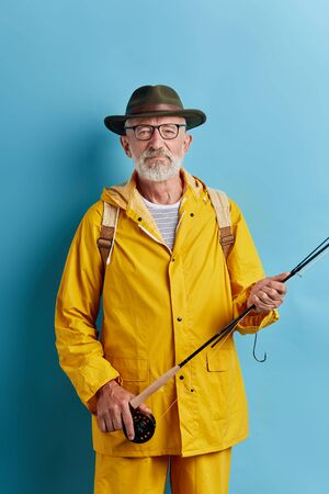 old bearded man in stylish clothes spending time on the bank of the river. close up photo