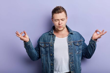 Young strong muscular bearded man wearing denim jacket, feels relaxed ,doing meditation gesture with fingers. Yoga concept.neditation, lifestyle, hobby, free time, spare time 版權商用圖片