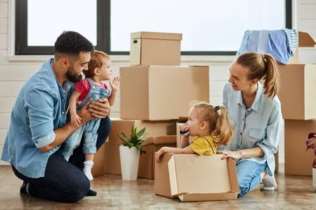 Caucasian family, man, woman and two girls play, smile with moving box. Father keep in hands youngest daughter, mother sat eldest daughter into box and play. In background boxes