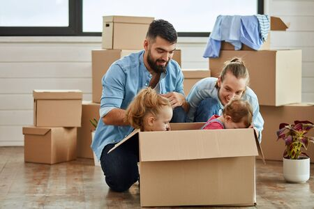 Happy caucasian family, man, woman and two girls play with moving box. Into it sit girls