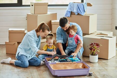 Happy caucasian family sit on floor, unpack suitcase in new house. Behind them carton boxes