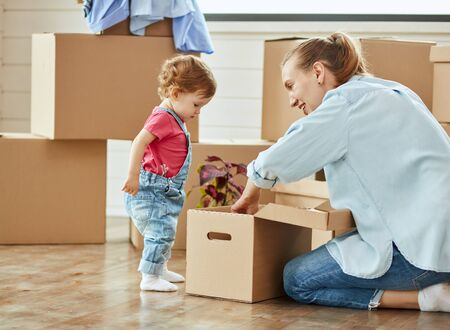 In center photo little child stand near box. Mother blonde woman wear blue shirt, jeans and white socks smile and show daughter something in box. Background moving boxes Zdjęcie Seryjne