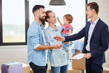Caucasian family of three people take keys new big house from realtor. They smile. Kid in mother hands play. Background moving boxes, big window.