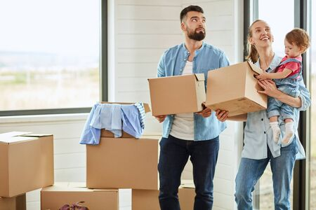 Bearded dark-haired man wear blue shirt enter house and keep box, fair-haired woman wear blue shirt keep boxes and child. Boxes in background