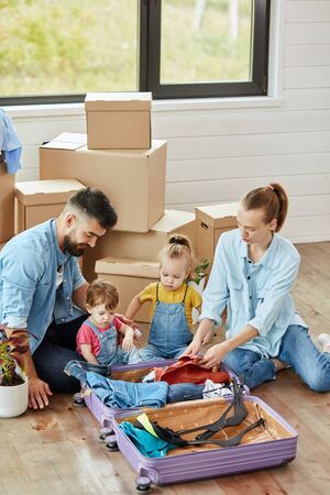Caucasian family, man, woman and two girls, sit on floor, unpack suitcase and smile in new house. Behind them moving boxes.