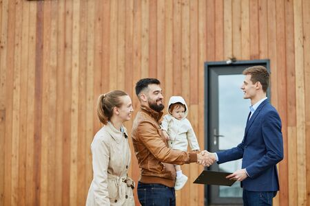 Caucasian happy family and realtor wear blue suit stand outdoor near new house just sold. Men shake hands.