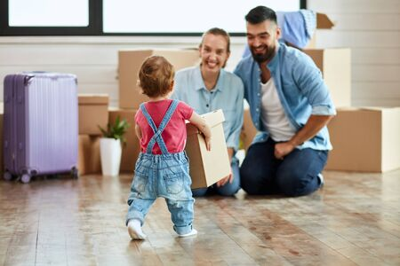 Kid wear denim overalls carries little moving box parents who sit on floor and smile