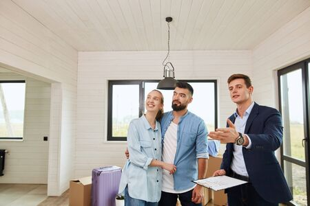 Realtor tells young couple about bright house. Moving boxes and suit in background.