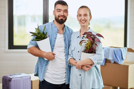 Caucasian couple wear blue shirt stand, smile, keep flowers in pot in new house. Great copy space. Background moving boxes, suitcase, window.