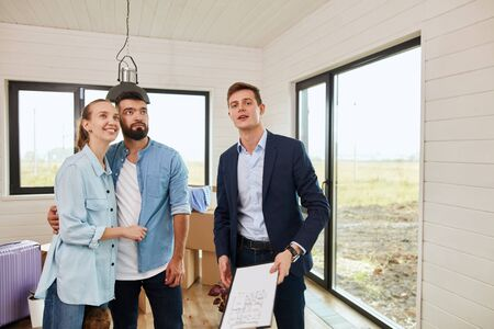 Caucasian couple and caucasian realtor wear blue jacket inspect new house for further purchase Zdjęcie Seryjne