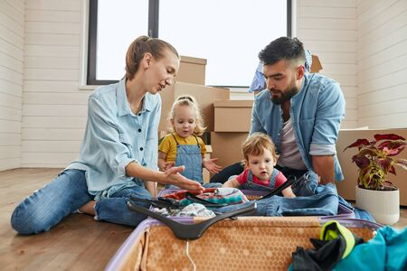 Happy caucasian family unpack suitcase on floor in new house. In foreground open suitcase with clothes hangers, jeans. Boxes for moving in background