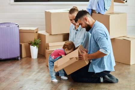 Couple wear blue shirt sit on floor. Kid wear denim overalls brought little moving box father. Family look into box, smile. Background moving boxes, suit and flower in pot Zdjęcie Seryjne