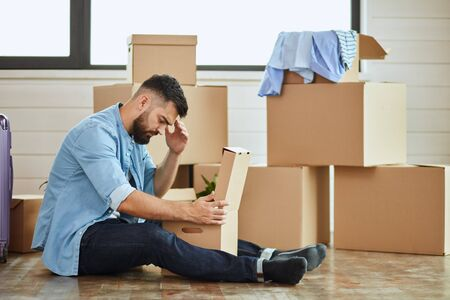 Caucasian man wear blue shirt sit on floor, unbox in new house. Background moving boxes, suitcase, window.