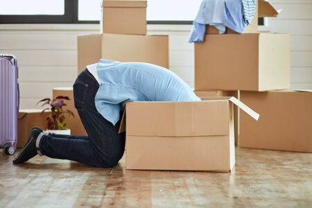 Caucasian man wear blue shirt sit on floor look deep into box in new house. Background moving boxes, suitcase, window.
