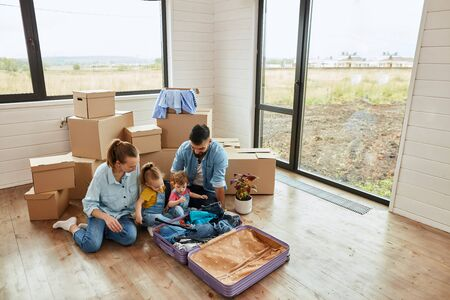 Above side view. Parents and two little daughters sit on floor and unpack family suitcase in new light house