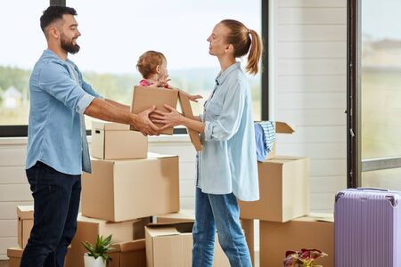 Bearded dark-haired man give daughter sit in box blonde-haired wife wear blue shirt, they smile. Baby pulls hands to mom. Background moving box, suitcase and big window