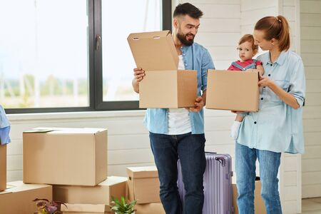 Bearded dark-haired man wear blue shirt enter house and keep open box, fair-haired woman wear blue shirt keep boxes and child. They look at each other and smile. Boxes and big window in background Zdjęcie Seryjne