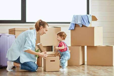 In center photo little child stand near box. Mother blonde woman wear blue shirt, jeans and white socks smile and look at daughter. Background moving boxes and suit