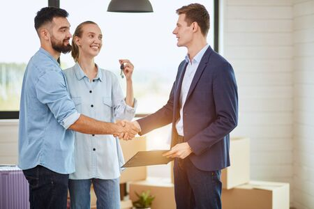 Young caucasian family and realtor conclude deal buy house. Men shake hands. Woman holds keys. Everyone smile. The sun shine. Zdjęcie Seryjne