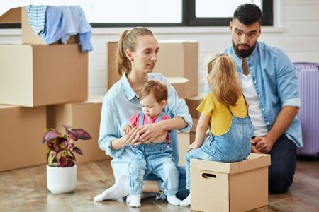 Family of four men sit on floor in guest room in just sell house. Background moving boxes, suit and flower in pot