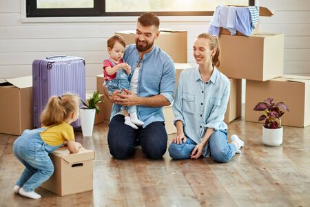 men sit on floor in guest room in just sell house. Eldest daughter wear yellow t-shirt and jumpsuit pushes box. Mom smile. Dad keep youngest daughter. Background moving boxes, suit and flower in pot