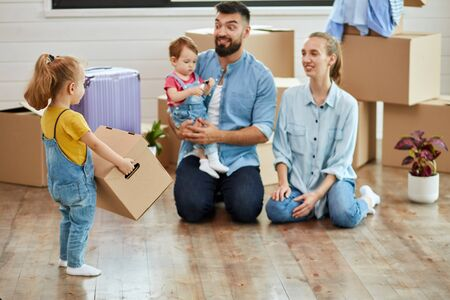 Family of four men sit on floor in guest room in just sell house. Eldest daughter wear yellow t-shirt and jumpsuit carries in hands box. Parents smile.