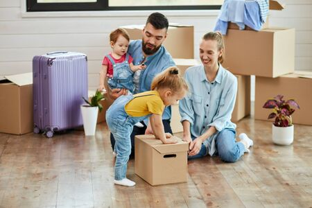 Family sit on floor in guest room in just sell house. Eldest daughter put box. Mom and dad smile. Dad keep youngest daughter. Background moving boxes, suit and flower in pot