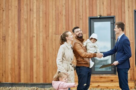 Caucasian happy family of four and realtor stand outdoor near new house just sold. Men shake hands.