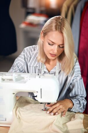 Young dressmaker sews clothes on sewing machine. small business. close up photo