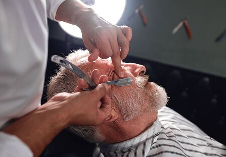 stylist touching his clients cheeck with finger, shaving facial hairs, close up cropped side view photo