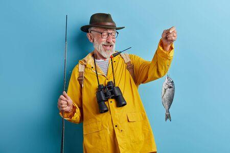 lächelnder Mann mit Brille mit Fernglas, der einen gelben Regenmantel und einen grünen Hut trägt, der seinen Hustenfiash anhebt, isolierter blauer Hintergrund, stsudio shot Standard-Bild