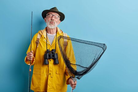 funny old man with binocular, rod and net in yellow raincaot and grren hat blowing kiss, whistling close up photo. isolated blue background, studio shot,
