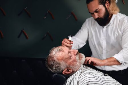 serious talented barber concentrated on brushing beard. close up photo. copy space