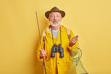 senior man has prepared to go fishing. close up photo. isolated yellow background, man holding fishing equipment