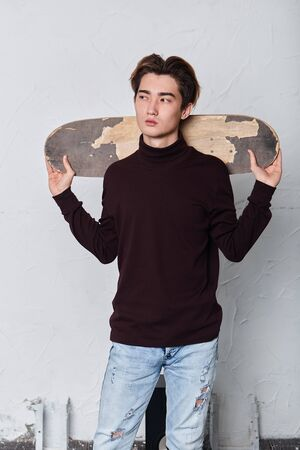 attractive serious cool man holding his skateboard preparing to ride, free time, close up photo.