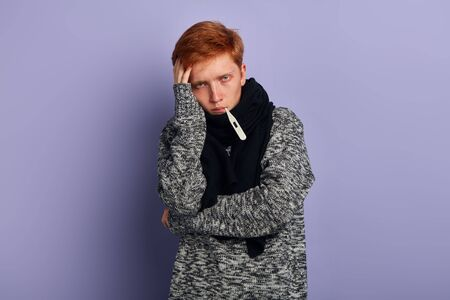 young red-haired man has high temperature, clotrait, isolated blue background, studio shot, close up portrait