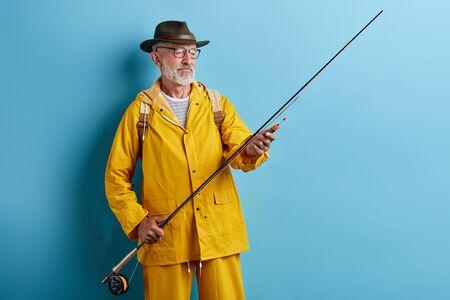 vieil homme à lunettes portant un élégant manteau jaune préparant la tige pour la pêche. gros plan photo. espace de copie. fond bleu isolé Banque d'images