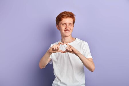 portrait of a young smiling man doing a heart gesture against a blue background. close up portrait I love , miss you, close up portrait