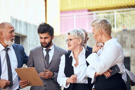Four caucasian businessmen portrait shooting wear different office wear discuss project outdoor