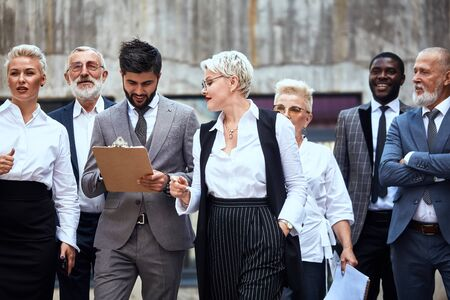 Six caucasian and one african businessmen dressed in stylish office clothes move in street. Woman pry as man make notice
