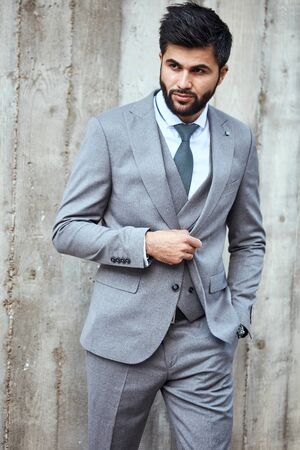 Adult caucasian brunet bearded businessman wear grey suit pose, keep one hand in pockets, another hand keep button on jacket. He move