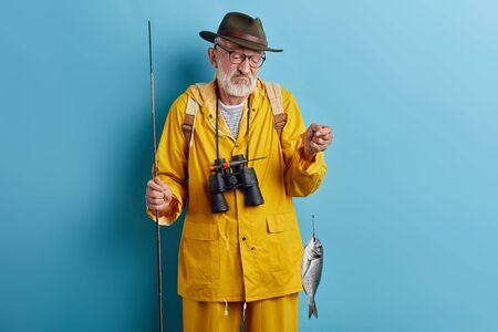 man is unhappy as he has poor catch, old man holding rod and looking at small fish in hand . isolated blue background, studio shot