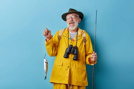 laughing smiling funny granny has cougfht fish for his wife, family, close up photo. luck, close up photo. isolated blue background, positive feeling and emotion